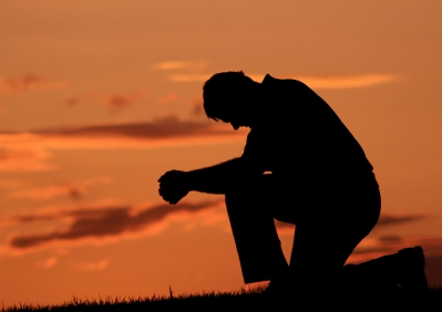 """Man kneeling: """"at the name of Jesus every knee should bow, in heaven and on earth and under the earth"""""""